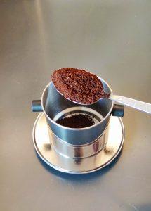 grob gemahlener, starker Kaffee wird in die Phin gegeben