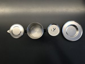 Ein Phin in seine Einzelteile aufgeteilt: der Deckel, der BEcher mit Sieblöchern, der Siebeinsatz und die Untertasse mit Sieblöchern