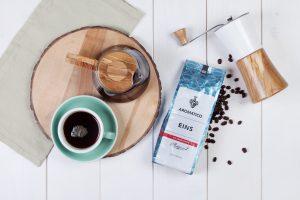 Kaffeepackung neben Kaffeemühle und Tasse