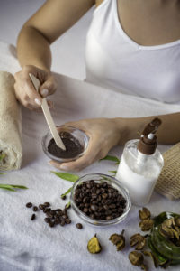 Young woman mixing ingredients for coffee facial mask for skin scrub treatment